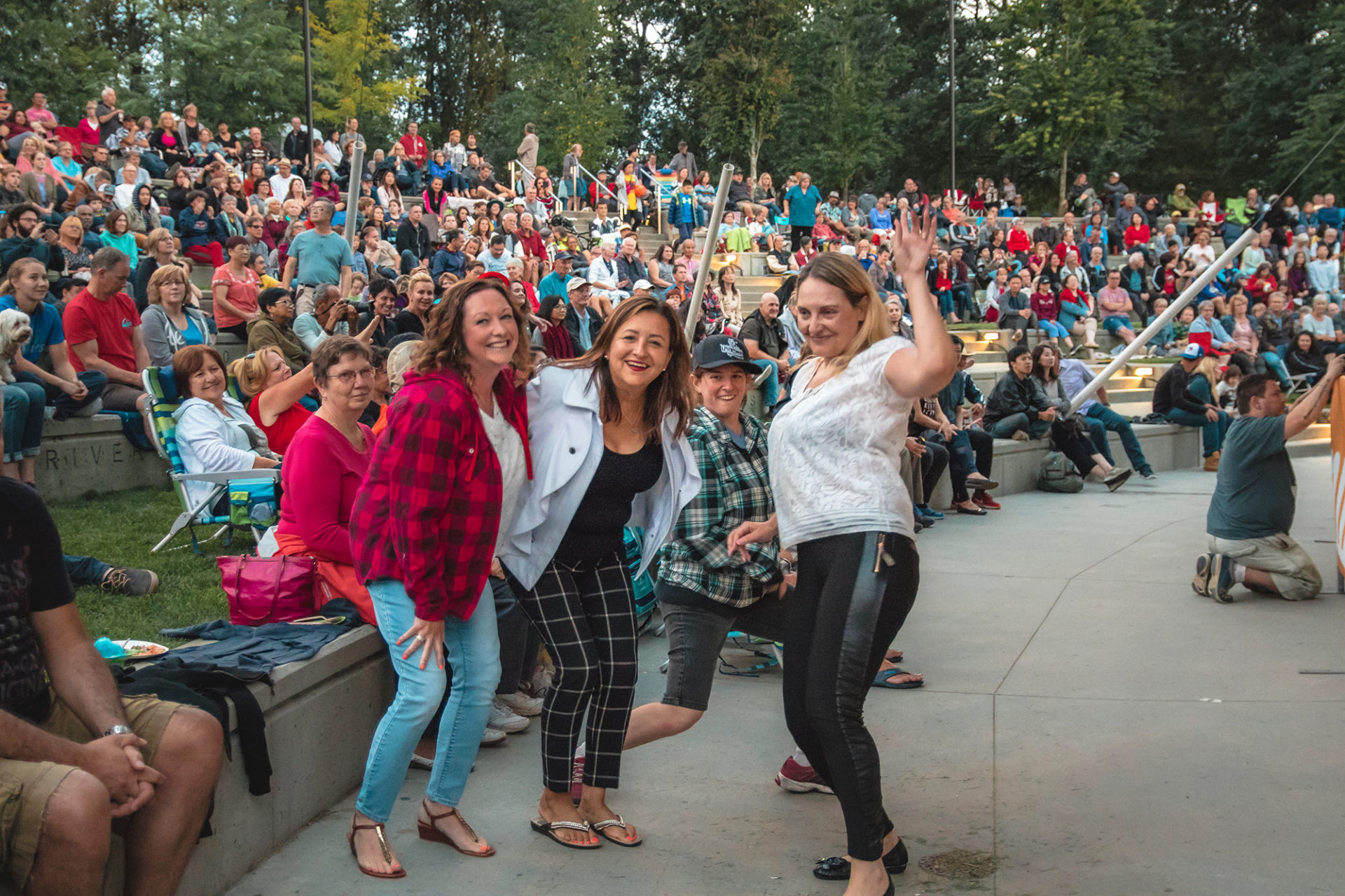 four woman making silly poses at concert