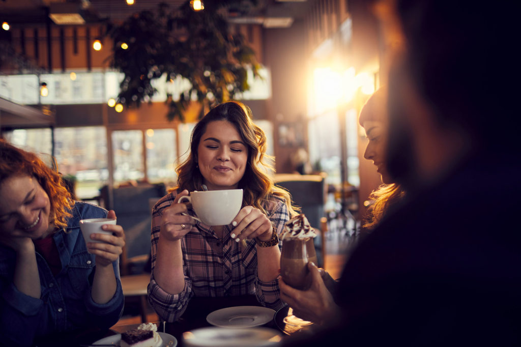 Woman holding a coffee cup, with friends in cafe
